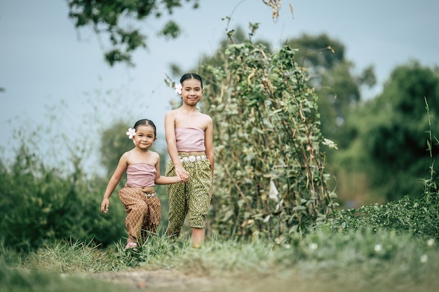 Porträt von zwei süßen mädchen in traditioneller thailändischer kleidung und weiße blume auf ihrem ohr, die hand in hand auf dem reisfeld geht, sie lächeln mit glück, kopienraum