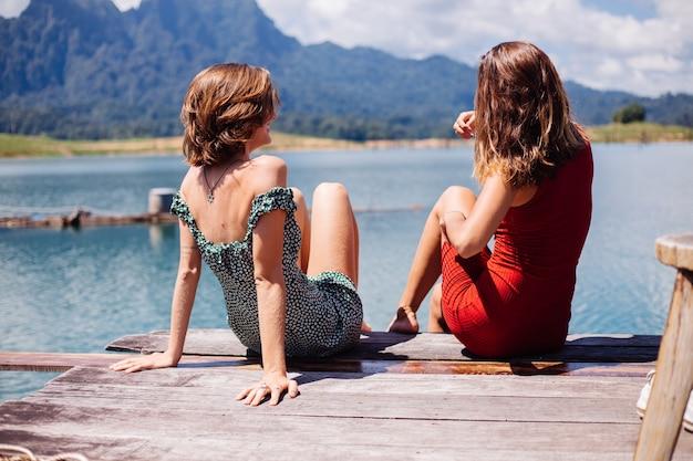 Porträt von zwei touristischen freundinnen in sommerkleidern auf urlaubsreise um thailand khao sok see mit schönem bergblick.