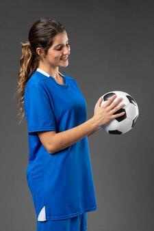 Porträt weiblicher fußballspieler mit ball Premium Fotos