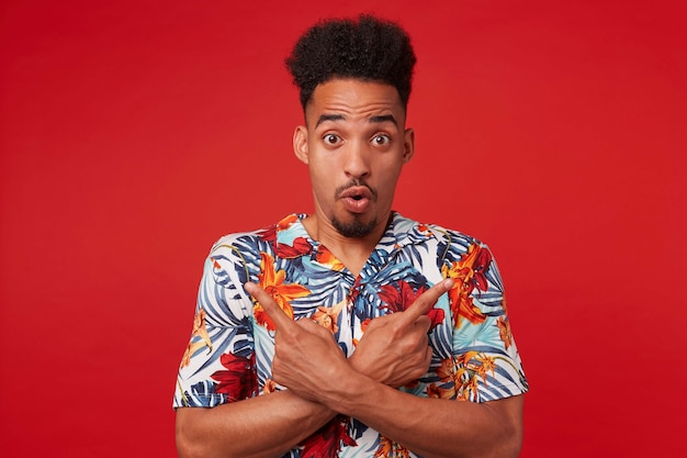 Porträt, wenn junger schockierter afroamerikaner im hawaiihemd, mit überraschtem ausdruck in die kamera schaut, über rotem hintergrund steht, in verschiedene richtungen zeigt.