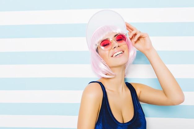 Porträt youful attraktive erstaunliche junge frau im blauen body, der auf blau-weiß gestreifter wand entspannt. tragen geschnittene rosa frisur, strandmütze, rosa sonnenbrille. glück, lächelnd.
