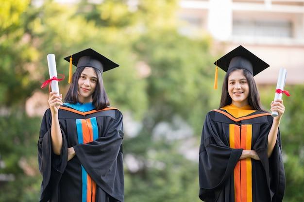 Porträt zwei absolventinnen, hochschulabsolventen mit diplom und glücklich