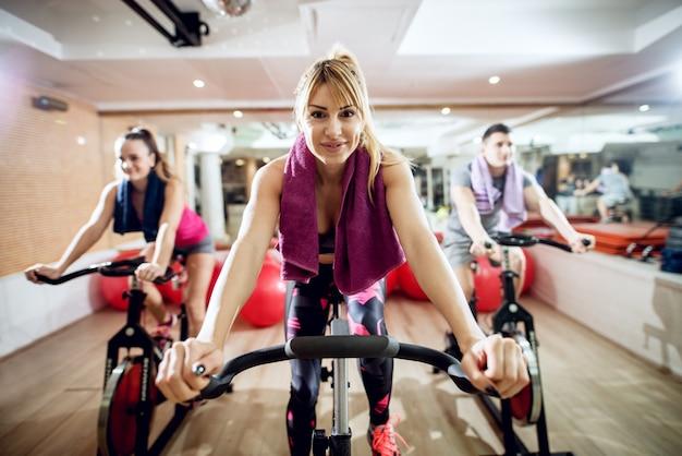 Porträtansicht der aktiven sportlichen fitnessgruppe der schönen gesunden form, die ein fahrrad mit handtüchern hinter dem hals im fitnessstudio reitet.