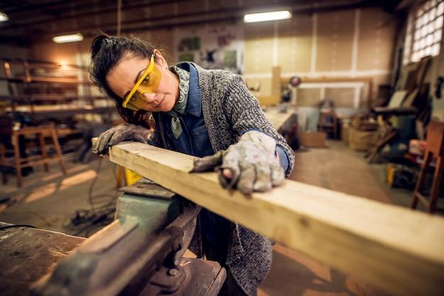 Porträtansicht der glücklichen attraktiven fleißigen professionellen zimmermannsarbeiterin mittleren alters, die holz in der werkstatt oder in der garage sucht und wählt.