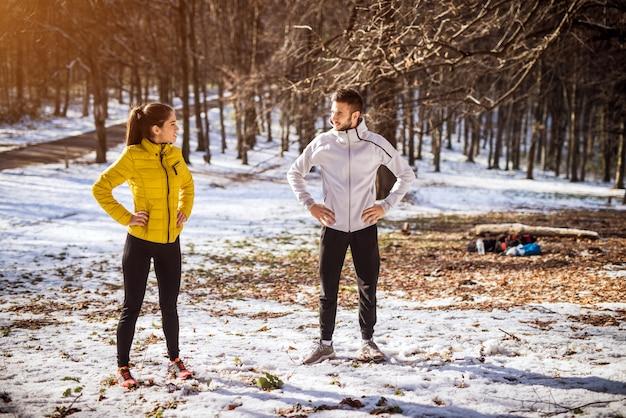 Porträtansicht des jungen attraktiven sportlichen paares in der sportbekleidung, die im park steht und einander vor dem laufen im kalten wintermorgen mit schnee herum schaut.