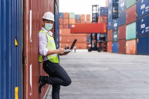 Porträtarbeiter mann, der eine laptop-waring-operationsmaske und einen sicheren weißen kopf verwendet, um für verschmutzung und viren am arbeitsplatz während der sorge um die covid-pandemie zu schützen