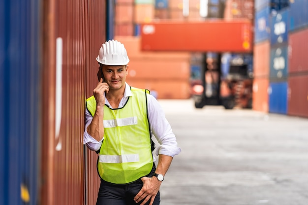 Porträtarbeiteringenieur, der unter verwendung eines mobiltelefons steht und die behälterbox vom frachtschiff zum export und import überprüft