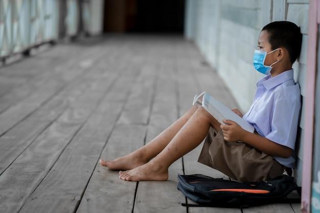 Porträtasiatische kinderschüler tragen gesichtsmaske, die an der grundschule sitzt.