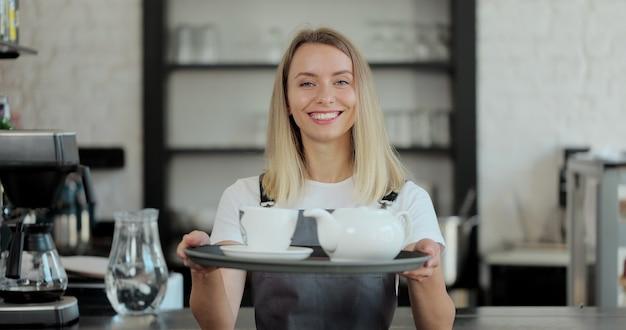 Porträtaufnahme der jungen schönen barkeeperin, die tassen kaffee auf dem hintergrund einer kaffeemaschine hält. service, geschäftskonzept.