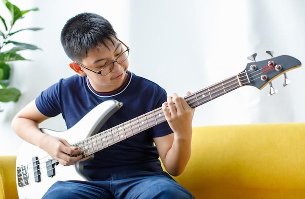 Porträtaufnahme eines hübschen lächelnden jungen mit brille, der das spielen der bassgitarre genießt. junior-bassist in freizeitkleidung, der auf der couch sitzt und ein instrument hält, während er in die kamera schaut