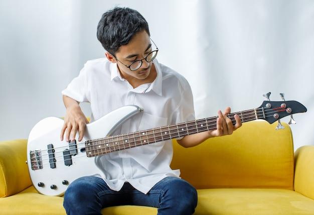 Porträtaufnahme eines hübschen lächelnden jungen teenagers, der das spielen der bassgitarre genießt. junior-gitarrist in freizeitkleidung, der auf der gelben couch sitzt und ein instrument hält, während er in die kamera schaut Premium Fotos