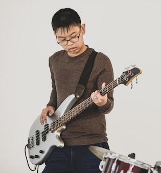 Porträtaufnahme eines jungen teenagers, der im studio bassgitarre spielt. professioneller juniorstudent, der ein instrument mit weißem hintergrund spielt. ein junger bassist, der für die show übt