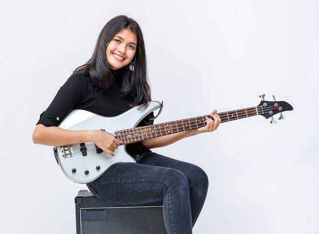 Porträtaufnahme eines süßen lächelnden jungen thailändisch-türkischen teenagers, der die bassgitarre spielt, während er auf dem verstärker sitzt. professioneller junior-gitarrist in die kamera schaut isoliert in weißem hintergrund