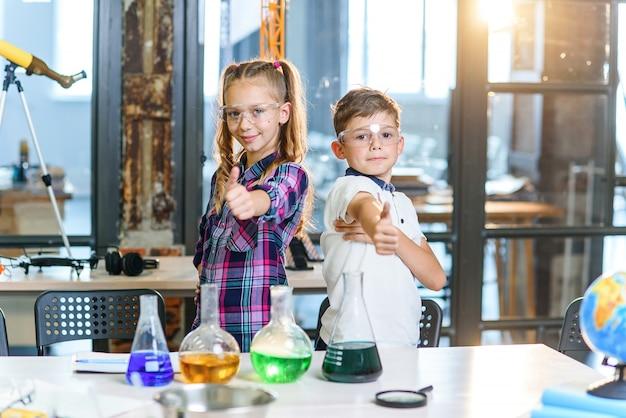 Porträtaufnahme von zwei fröhlichen kaukasischen wissenschaftlern in schutzbrillen, die daumen hoch in der chemischen klasse der grundschule zeigen