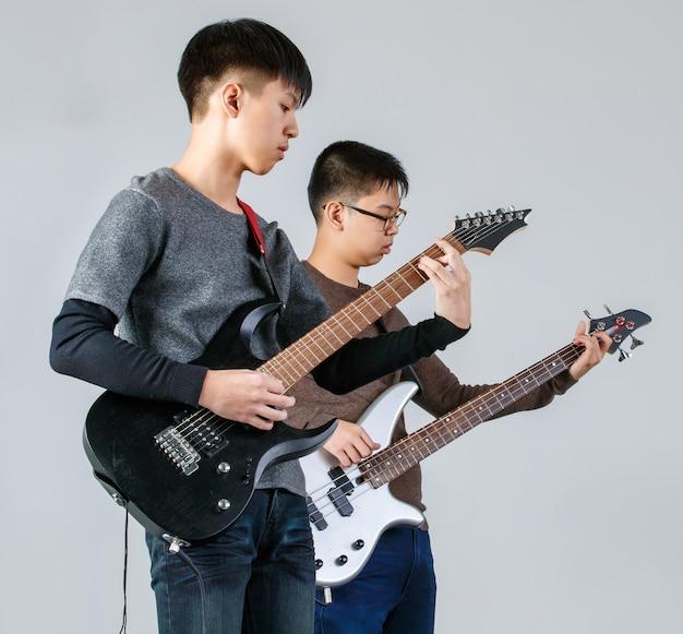 Porträtaufnahme von zwei jungen schulfreunden im teenageralter, die zusammen musik spielen. professioneller junior-gitarrist und bassist, der eine e-gitarre und eine bassgitarre spielt, isoliert mit weißem hintergrund