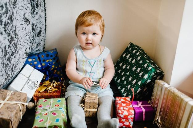 Porträtbaby, das mit spielzeug spielt, sitzt auf den hintergrundgeschenken frohe weihnachten