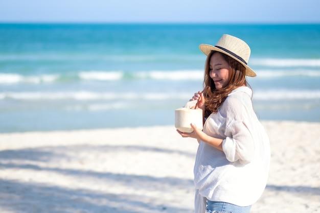 Porträtbild einer schönen asiatischen frau, die kokosnusssaft am strand hält und trinkt