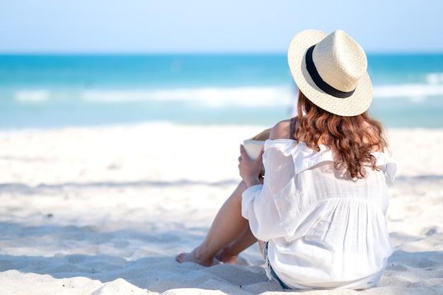 Porträtbild einer schönen asiatischen frau genießen, kokosnusssaft am strand zu sitzen und zu trinken