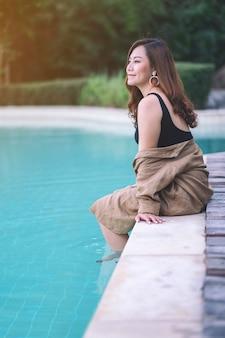 Porträtbild einer schönen asiatischen frau genoss das sitzen am schwimmbad