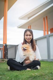 Porträtbild, jugendlich frau, die mit pomeranian hund im haus, asiatische frau spielt