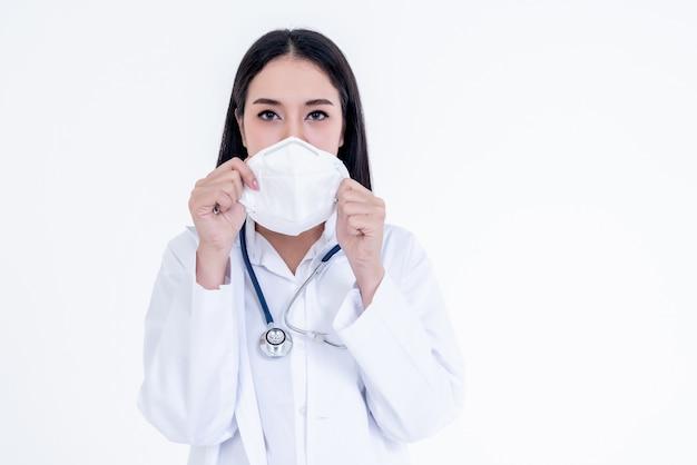 Porträtbilder der asiatischen ärztin, die eine maske mit weißem hintergrund hält