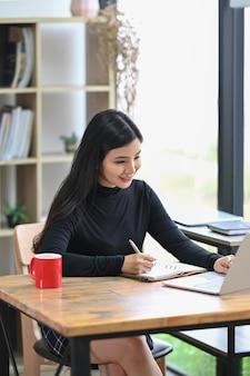 Porträtdesigner der jungen frau mit laptop-computer beim sitzen am kreativen arbeitsplatz.