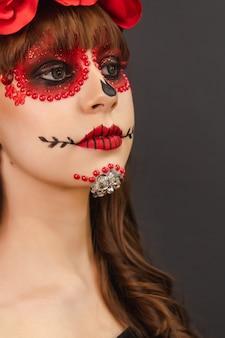 Porträtdetail eines schönen mädchens mit make-up dia de los muertos mit grauem hintergrund.