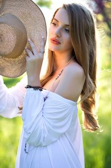Porträtempfindliche junge hübsche frau mit langen haaren, im attraktiven hellen weißen kleid, das sommerhut hält und sonnenlicht mit geschlossenen augen genießt. wahre positive emotionen, inspirationen ausdrücken