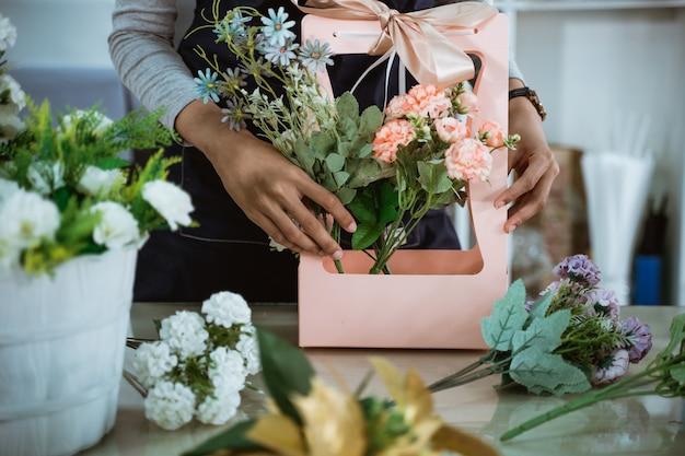 Porträtflorist, der eine geschenkblume auf tischarbeitsplatz für kunden vorbereitet