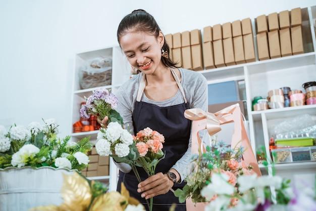 Porträtfloristin, die eine geschenkblume auf tischarbeitsplatz für kunden vorbereitet