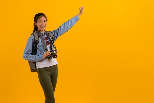 Porträtfoto der jungen attraktiven asiatischen touristischen frau auf gelb