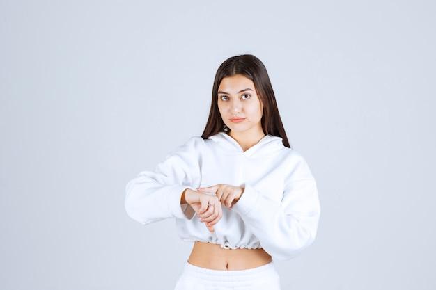 Porträtfoto des modells des recht jungen mädchens, das auf ihr handgelenk zeigt.
