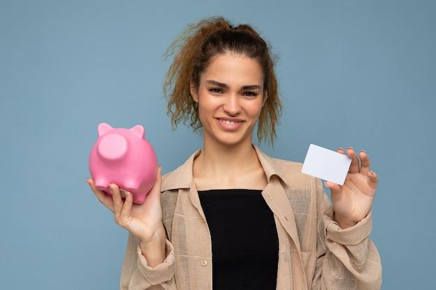 Porträtfoto einer glücklichen, positiv lächelnden jungen, schönen, attraktiven, brünetten frau mit aufrichtigen emotionen, die ein stylisches beige hemd trägt, isoliert auf blauem hintergrund mit kopienraum, hält rosa schwein
