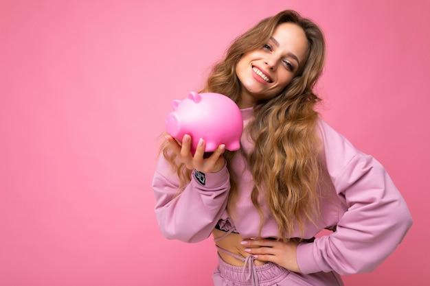 Porträtfoto einer glücklichen, positiv lächelnden jungen schönen attraktiven frau mit welligem, langem blondem haar mit aufrichtigen emotionen, die einen trendigen rosa hoodie einzeln auf rosafarbenem hintergrund mit kopienraum trägt und