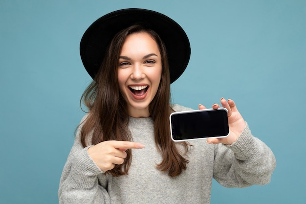 Porträtfoto einer schönen jungen frau mit schwarzem hut und grauem pullover mit telefon, das smartphone auf dem hintergrund isoliert zeigt