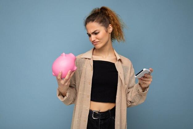 Porträtfoto einer unzufriedenen jungen schönen attraktiven brünetten frau mit aufrichtigen emotionen, die ein beigefarbenes hemd einzeln auf blauem hintergrund mit kopienraum trägt, hält rosa sparschwein und