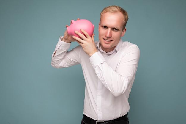 Porträtfoto eines nachdenklichen, positiv lächelnden jungen, gutaussehenden blonden mannes mit aufrichtigen emotionen, der trägt