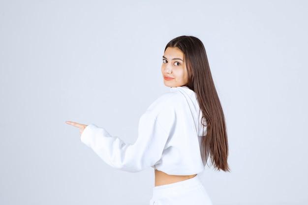Porträtfoto eines netten modells des jungen mädchens, das weg steht und zeigt.