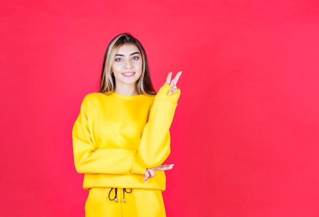 Porträtfoto eines positiven mädchenmodells, das steht und siegeszeichen zeigt