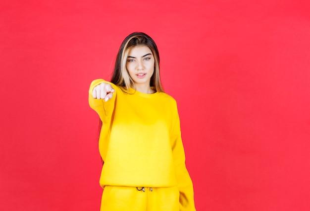 Porträtfoto eines schönen mädchenmodells stehend und auf kamera zeigend
