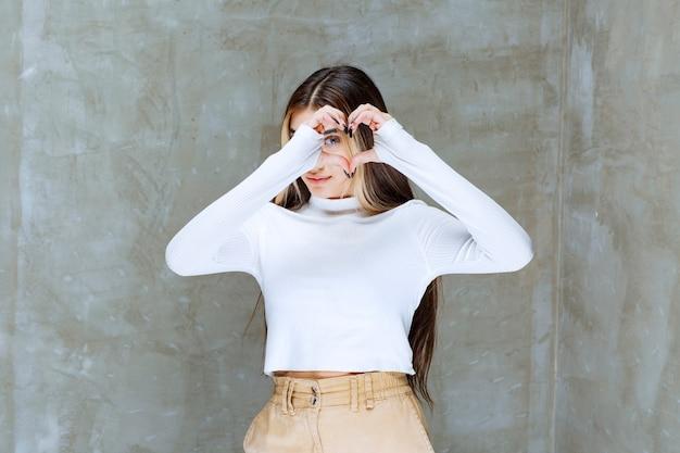 Porträtfoto eines stehenden und zeigenden herzens eines lächelnden mädchenmodells mit zwei händen