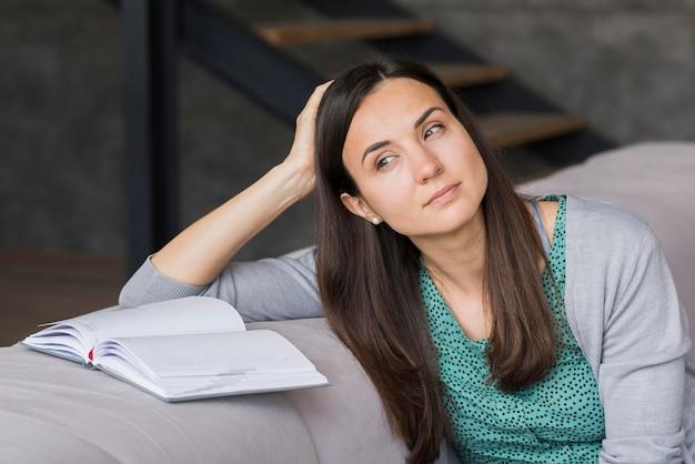Porträtfrau auf der couch beim lesen