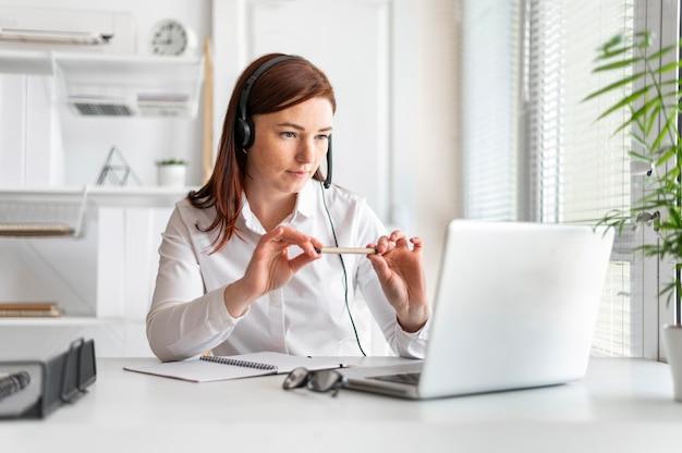 Porträtfrau bei der arbeit, die videoanruf auf laptop hat