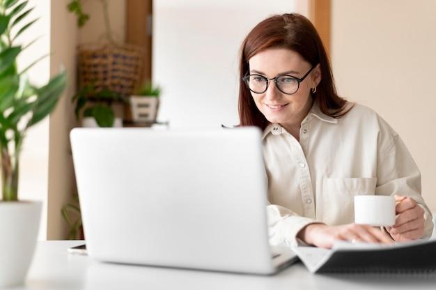Porträtfrau bei der arbeit, die videoanruf hat