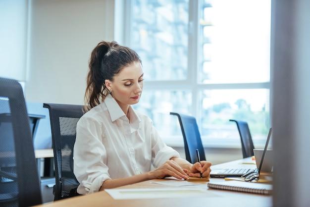 Porträtfrau, die am laptop arbeitet