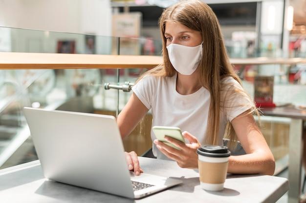 Porträtfrau, die am laptop mit maske arbeitet