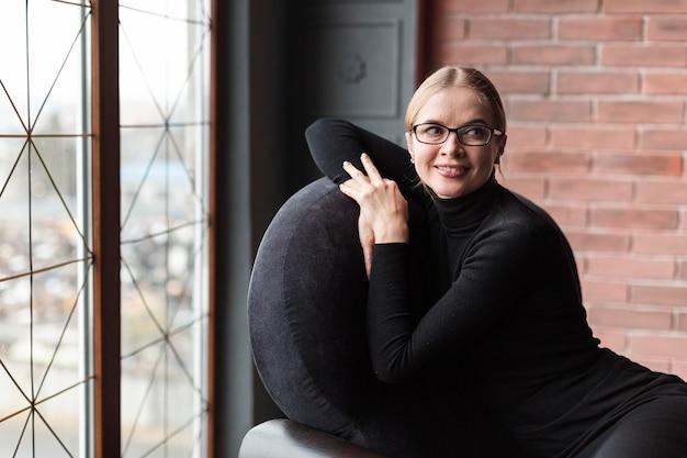 Porträtfrau, die auf couch sitzt