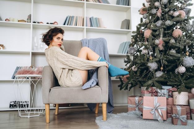 Porträtfrau, die auf dem stuhl nahe weihnachtsbaum sitzt