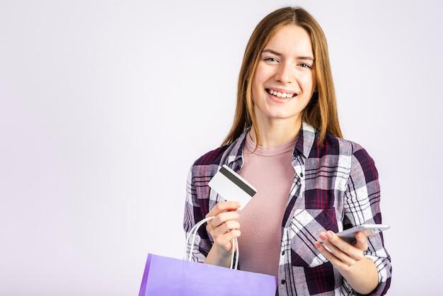 Porträtfrau, die eine tasche hält und kamera betrachtet