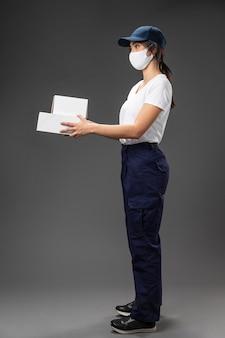 Porträtfrau, die für lieferservice arbeitet maske trägt